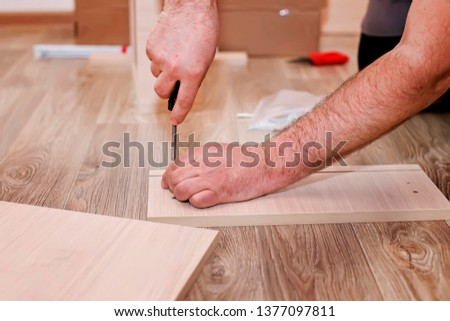 Handyman service in the process of assembling furniture. Assembly kitchen closets and cabinets from wood and chipboard particles. Home woodworks - fixing with a cordless screwdriver and mounting