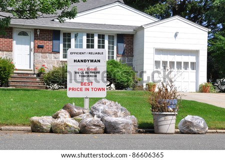 Handyman Sign on Front Yard Lawn of Suburban Home behind Plastic Bags of Trash on Street Curb in Residential Neighborhood