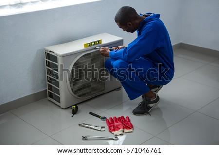 Handyman testing air conditioner at home