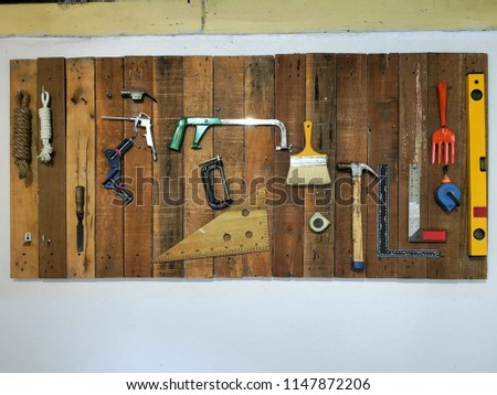 Handyman tool equipment on the wooden broad contain Chisel, Pliers, Rope, Axe, Hammer, Hacksaw, Knife, Brush, Ruler, Rake, Wrench and Screwdriver.