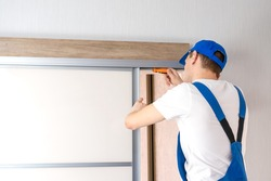 Handyman who installs sliding doors at home in overalls with a screwdriver in his hands repairs the door