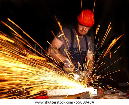 handyman with electric grinder on duty, industrial background