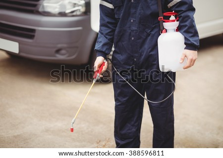 Handyman with insecticide standing in front of his van