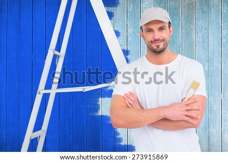 handyman with paintbrush and ladder against wooden planks