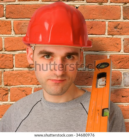 handyman with red hat and a brick wall as background