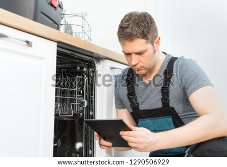 Handyman with tablet pc repairing domestic dishwasher in the kitchen. #1290506929