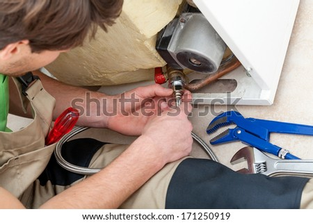 Handyman with tools repairing an equipment in boiler room