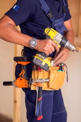 Handyman with yellow headphones works with drill does repair.