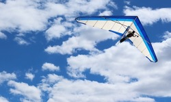 Hang Glider flying in Kitty Hawk North Carolina on a clear, bright, blue sunny day with clouds in the sky