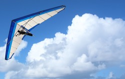 Hang Glider flying through the sky white puffy clouds