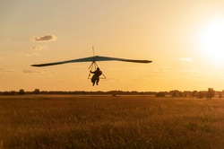 Hang glider landing on the sunset. Beauty of extreme sports. Dream to fly and learning to fly concept