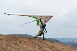 Hang glider pilot runs on the slope with his wing. Extreme sport
