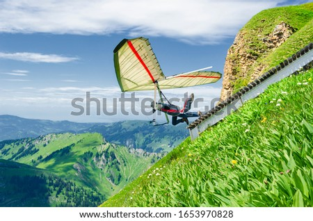 Hang glider pilots runs from steep slope high in the mountains. Diedamskopf, Austria. Extreme airborne sport. Сток-фото ©
