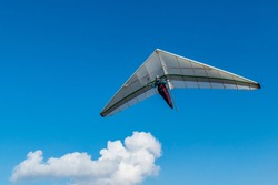 Hang glider wing and blu sky with white cloud. Dream of flying come true.