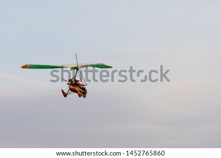 Hang gliding high up in the air amongst the clouds, extreme sports and recreation background with copy space. Two people fly togetherness recreational activity hang glide outdoors adventure concept. #1452765860