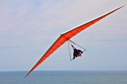 Hang gliding man on an orange wing with sky in the background