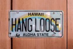 Hang Loose Hawaii Aloha State License Plate tacked up against a cedar wall, Ontario, Canada.