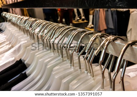 Hangers with clothes in a row in the store. Things on hangers.