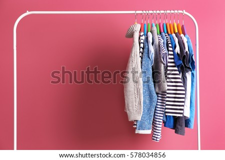 Hangers with colourful clothes on pink background #578034856