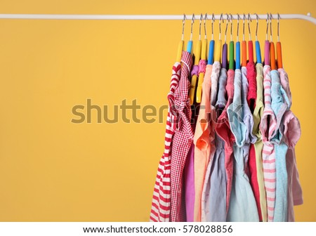 Shutterstock Hangers with colourful clothes on yellow background