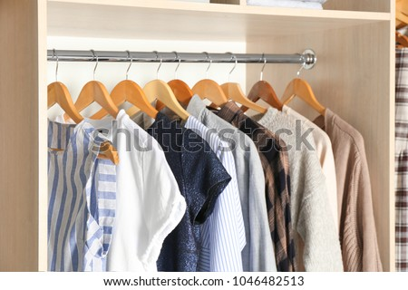Hangers with different clothes in wardrobe closet #1046482513