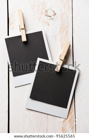 Hanging aged photo frames on wooden background