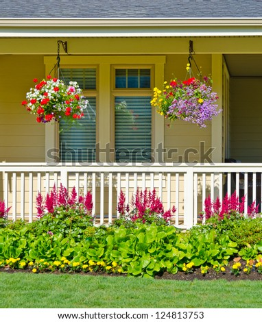 Hanging baskets of flowers at the front porch. Landscape design.