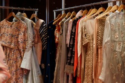 Hanging beautiful indian dresses different colors and decoration at market, shop, boutique, bazaar, fashion clothes designer collection