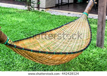 hanging bench seat chair cradle hammock in basket design on the green grass field #442428124
