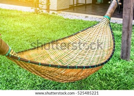 hanging bench seat chair cradle hammock in basket design on the green grass field #525485221