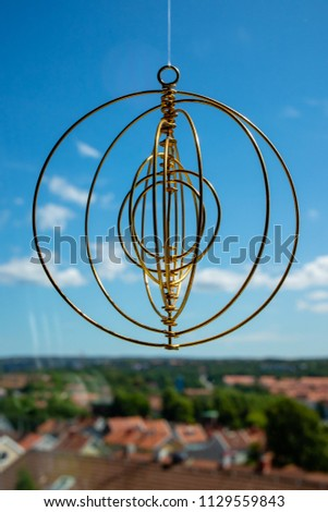 Hanging brass ornament with several circles against a blue sky with a city in the baground