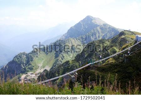 Hanging bridge on Rosa Peak in Rosa Khutor, Sochi, Caucasus, Russia. An extreme tourist walks on a suspension bridge at Rosa Peak.