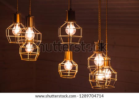 Hanging bulb lamps. Chandelier with yellow LED lighting elements covered with metal wire frame lampshades, photo with selective focus #1289704714