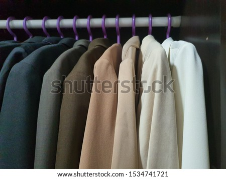 Hanging clothes. Suit jackets in black cabinets come in many colors, including black, gray, brown, white, long-sleeved suits. Clothes hanger with clothes.