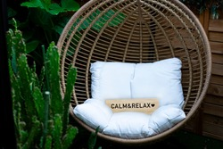 Hanging garden chair  with cactuses and a sign that say