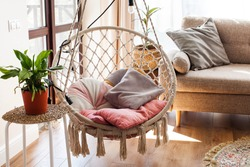 Hanging home rope swing in a Scandinavian interior. The concept of home life, hugge, home comfort.