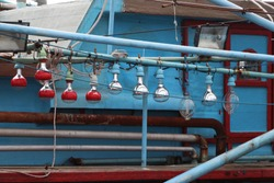 Hanging light bulb on the blue fishing boat.