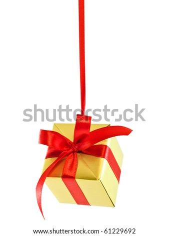Hanging on a ribbon golden gift wrapped present with red satin bow isolated on white