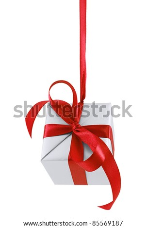 Hanging on a ribbon silver gift wrapped present with red satin bow isolated on white