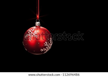 hanging red dull christmas ball on black background