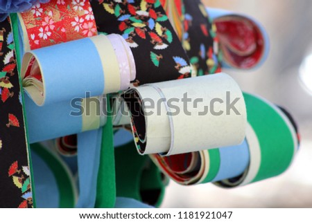 hanging rolls of Japanese origami and washi paper. Colorful strips of patterned paper bundled together.  Japanese arts and crafts paper for tanabata #1181921047