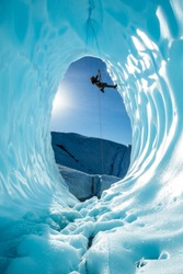 Hanging sideways with one foot out on the wall, an ice climber ascends a rope from a large blue ice cave on the Matanuska Glacier. Water drips down everywhere as the sun melts the ice of the glacier.