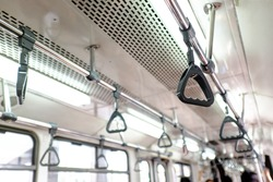 hanging straps or grab handles inside a metro train