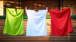 Hanging T-shirts Compose the Italian Flag: Green, White and Red (Tricolore). Typical Italian Balcony at Sunset. The Shirts Are Unbranded