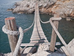 hanging wooden bridge connect rocky sea cost