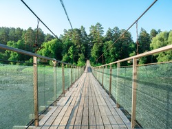 Hanging wooden bridge on steel ropes inside view. Suspension bridge against a background of green forest and blue sky, bridge through the River Ay, Bashkortostan, Russia.