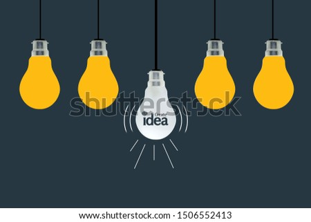 Hanging yellow light bulbs with glowing one different idea on dark blue background , Minimal concept idea, creative idea, create idea concept.
