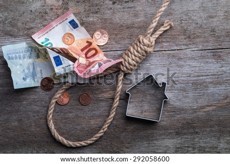 Hangman\'s noose with house, keys and money on brown wooden background