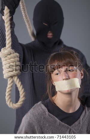 hangman with noose and female victim over grey background