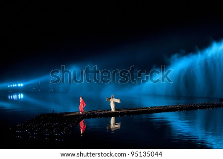 HANGZHOU, CHINA - NOVEMBER 26: Artists perform in Zhang Yimou's outdoor folk musical show 'Impressions West Lake' in an outdoor theatre built in the lake on November 26, 2011 in Hangzhou, China.